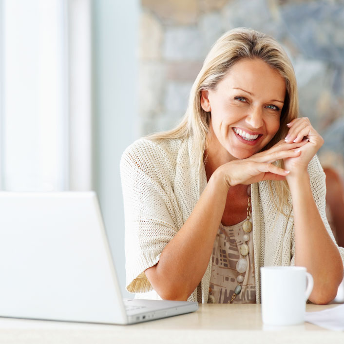 blonde lady sitting at desk with coffee and computer