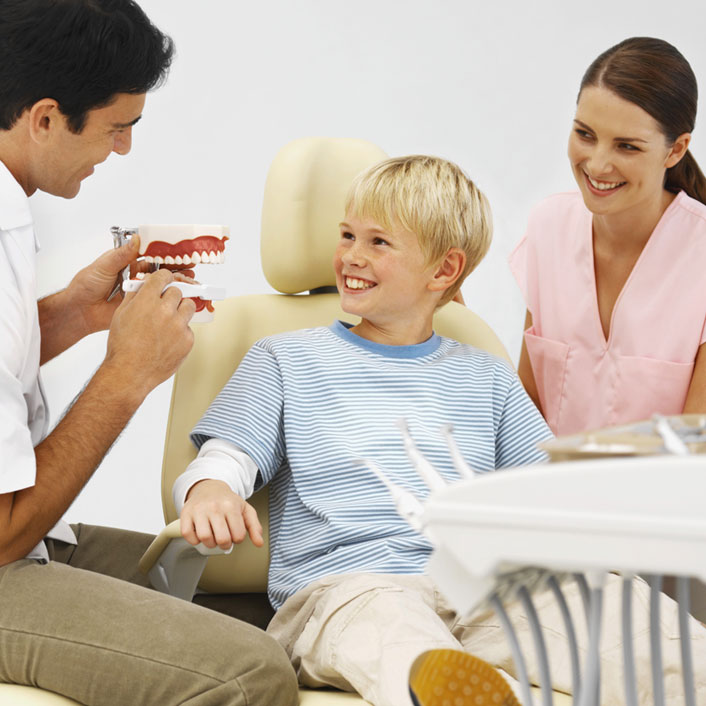 picture of child smiling in dentist chair with dentist and hygenist