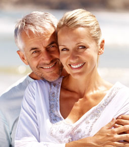 senior white couple smiling on beach